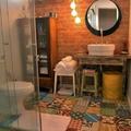 Banho social com ladrilhos hidráulicos e parede de tijolinho