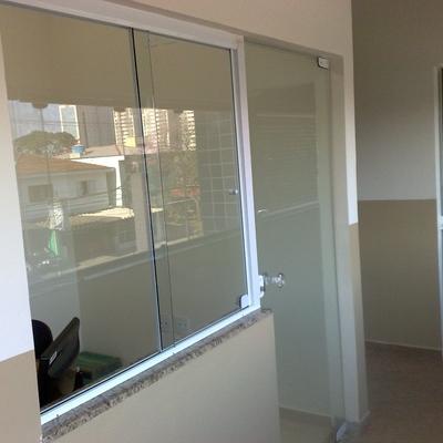 Janela com moldura em alumínio e porta em vidro temperado.