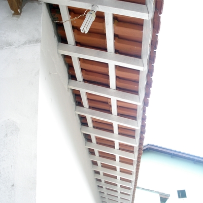 Pintura de madeiramento do beiral de uma casa.