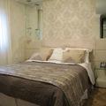 Quarto de Casal de Cliente - Cabeceira de cama tapeçada e criado mudo com vidro.