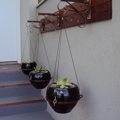 Hall de acesso com vasos vietnamitas pendurados em mão-francesa e quadro de deck cumaru.