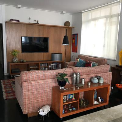 Sala de TV com painel de madeira e decoração descontraída